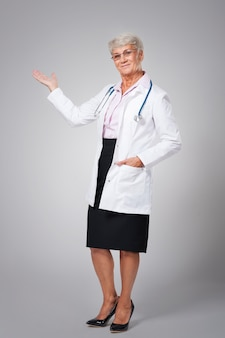 Smiling female doctor pointing at copy space