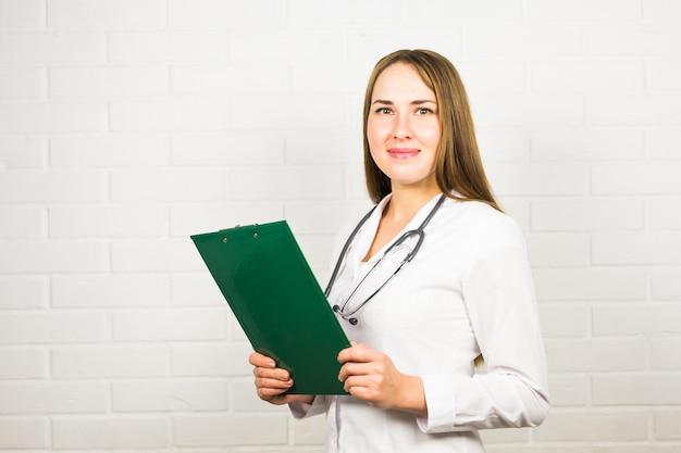 Улыбающиеся женщина-врач с папкой в форме стоял в больнице
