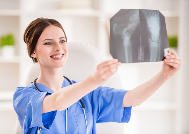 Smiling female doctor with stethoscope looking at x-ray.