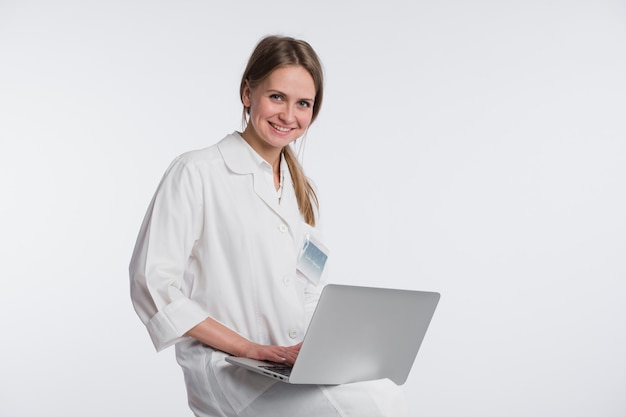 Smiling female doctor working on her laptop against a white