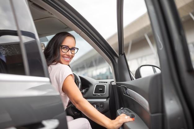 Улыбающаяся женщина-водитель открывает дверь машины с правым рулем перед торговым центром.