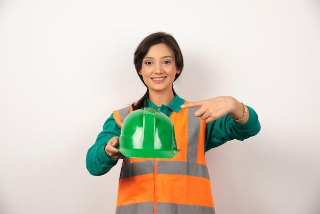 白い背景の上のヘルメットを保持している笑顔の女性エンジニア。