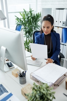 Smiling female entrepreneur analyzing data in sales report when working at office desk