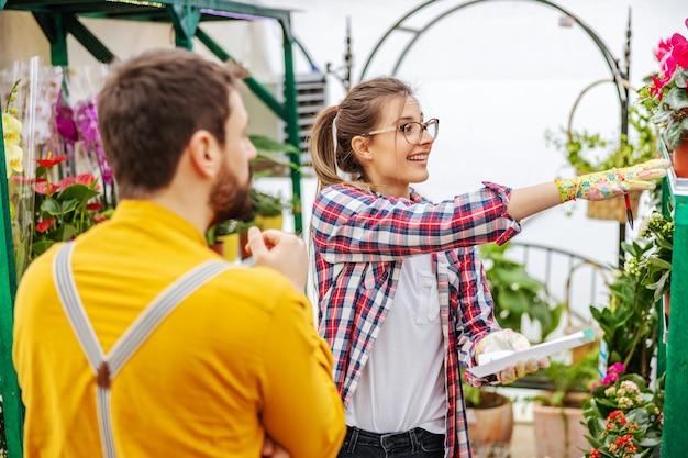 顧客に花を提供する笑顔の女性起業家。温室のインテリア。