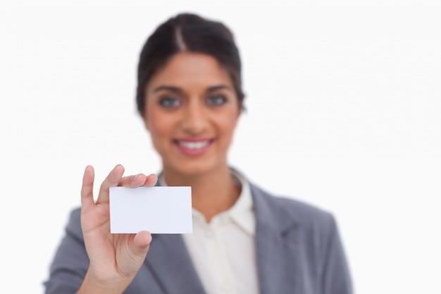 Улыбается женщина-предприниматель, показывая свою визитную карточку
