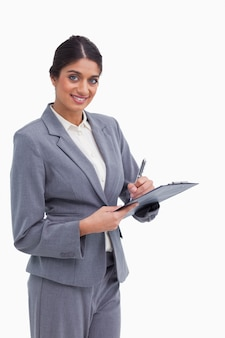 Smiling female entrepreneur with clipboard and pen