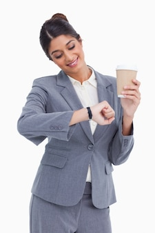 彼女の時計を見て紙カップで女性の起業家を笑顔