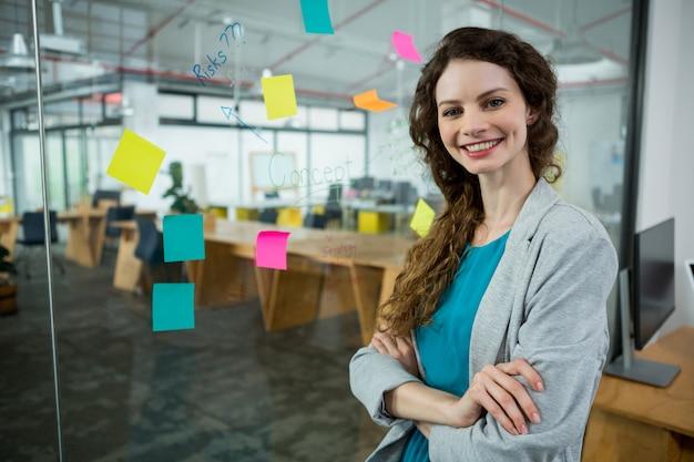腕を組んで立っている笑顔の女性幹部がクリエイティブ・オフィスで交差