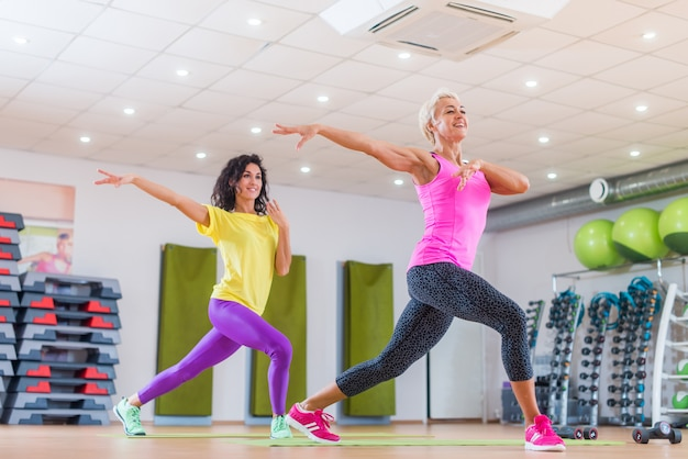 Smiling female fitness models working out in gym doing cardio exercise, dancing zumba.