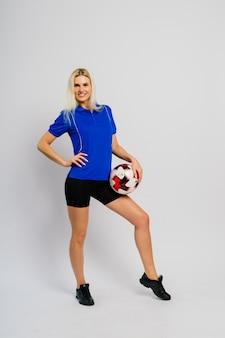 흰색 배경에 고립 된 공을 웃는 여성 축구 선수