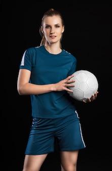 검은 배경에 고립 된 축구 공으로 웃는 여자 축구 선수