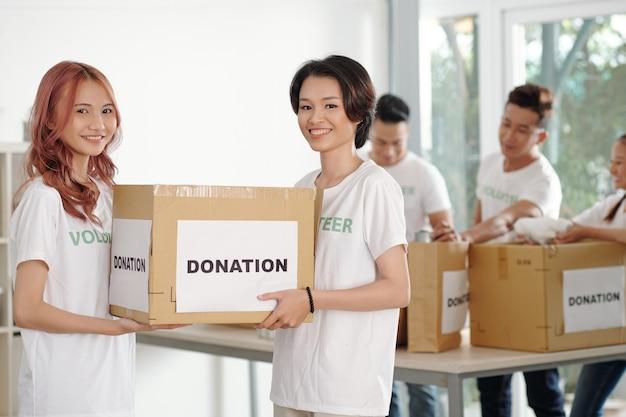 기부된 옷이 든 큰 상자를 들고 웃는 여자 친구, 배경에서 물건을 분류하는 동료