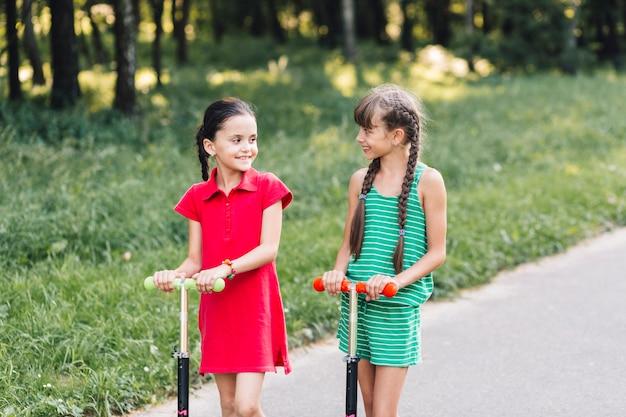 Amici femminili sorridenti che se lo esaminano nel parco