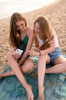Smiling female friends looking at mobile phone sitting at beach