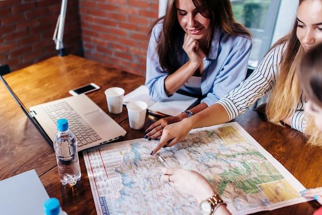 地図上の目的地を探して休暇を計画して机に座っている女性の友人の笑顔