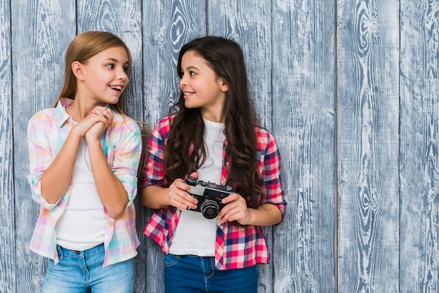 Smiling female friends standing against grey wooden wall looking at each other