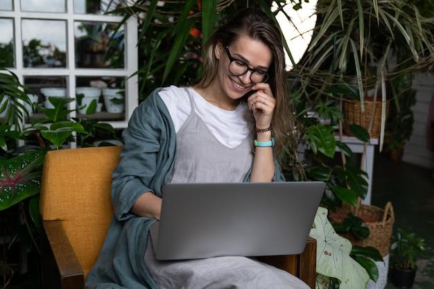 緑の家の椅子に座って、ラップトップを使用して、webコールで話す女性庭師の笑顔