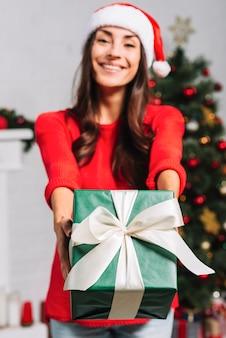 Smiling female giving present box