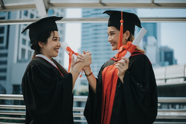 그녀의 친구와 함께 웃는 여성 대학원 핸드 쉐이킹 프리미엄 사진