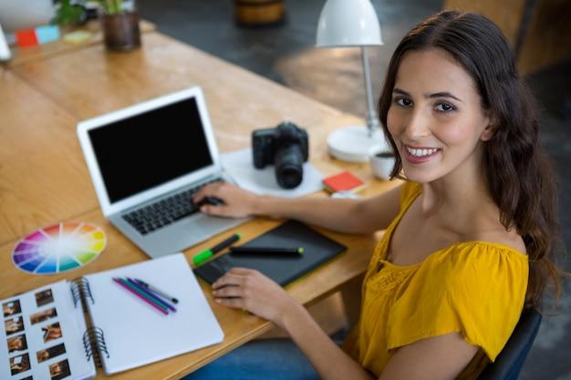 Улыбающийся женский графический дизайнер с помощью ноутбука