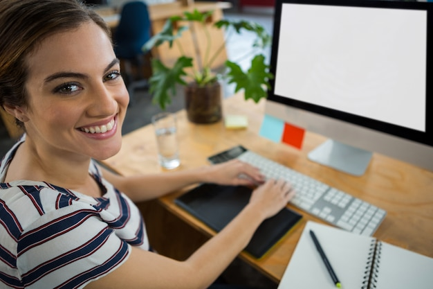 Smiling female graphic designer working on computer