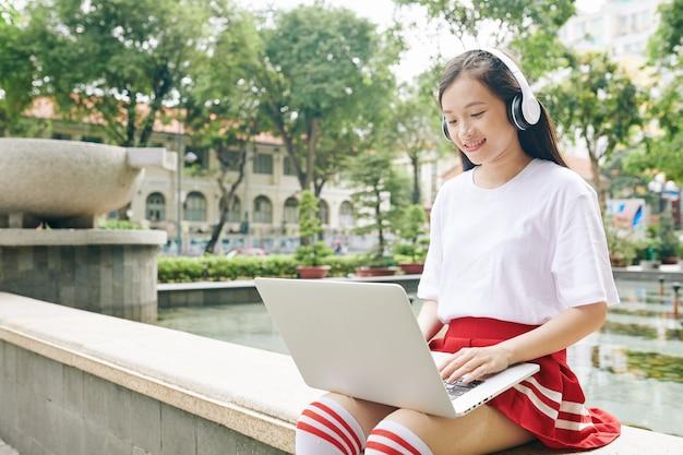 Улыбающаяся студентка средней школы смотрит вебинар на ноутбуке, сидя у фонтана в парке