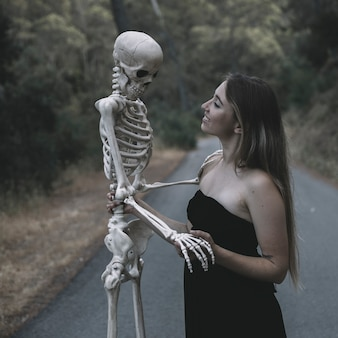 Smiling female holding artificial skeleton of man standing on road
