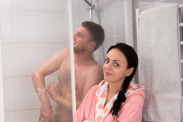 목욕 가운을 입은 웃고 있는 여성이 남자친구를 기다리는 동안 욕실에 투명한 유리문이 있는 샤워실에서 샤워를 하고 있습니다