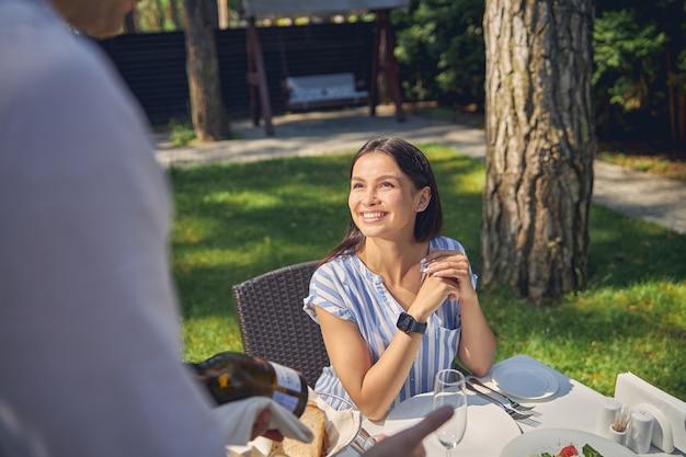 녹색 정원에서 햇빛이 하루에 식탁에 앉아 캐주얼 의류에 웃는 여성