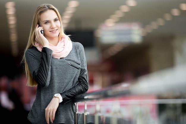 携帯電話で話す現代的な大きな建物で女性を笑顔