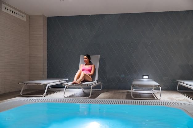 Улыбающаяся женщина в розовом купальнике сидит на шезлонге возле бассейна с пузырьками и наслаждается выходными на спа-курорте
