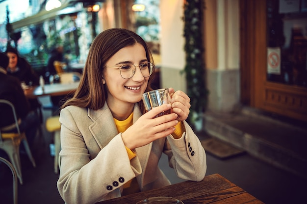 Smiling female influencer sitting on terrace of bar, holding cup of tea and warming up hands.