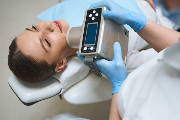Smiling female is lying in chair and enjoying teeth treatment with electronical machine in modern clinic