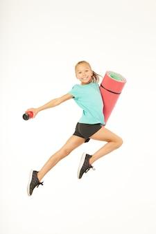 공중에서 점프하는 동안 운동 매트와 스포츠 음료를 들고 웃는 여자 아이. 흰색 배경에 고립