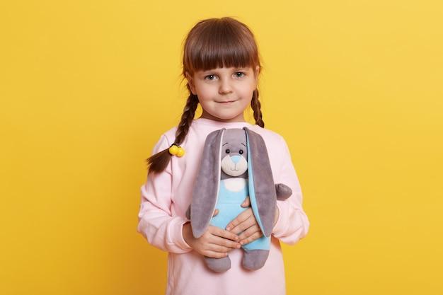 노란색 배경 위에 절연 포즈를 취하는 창백한 돼지 셔츠를 입고 땋은 여성 아이를 웃고, 손에 부드러운 토끼 장난감을 들고 카메라를 직접보고, 아이는 그녀의 장난감을 가지고 노는 아이.