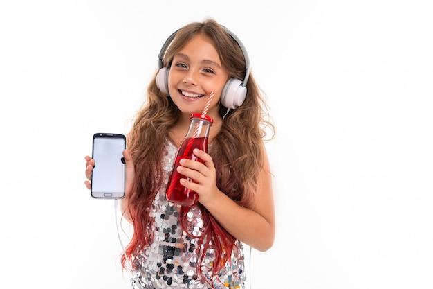 Улыбающаяся девочка с смартфоном и безалкогольным напитком в руках