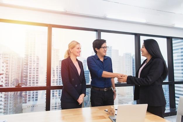 オフィス、不動産、投資購入取引のコンセプトで多民族のカップルの顧客と握手する笑顔の女性弁護士またはファイナンシャルアドバイザー