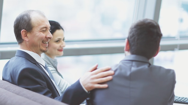 Smiling female and male business leaders handshaking over desk
