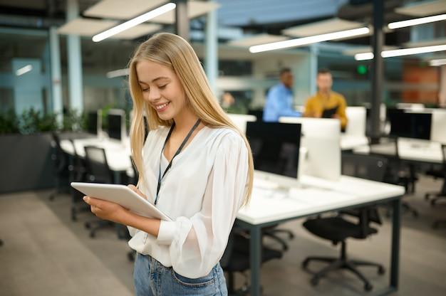 웃고 있는 여성 관리자는 노트북, it 사무실 내부를 배경으로 들고 있습니다. 전문 작업자, 계획 또는 브레인스토밍. 현대 회사의 성공적인 직원