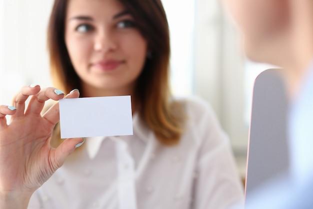 Улыбающиеся женщина менеджер, показывая ее визитную карточку