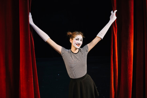 Smiling female mime artist holding red curtain