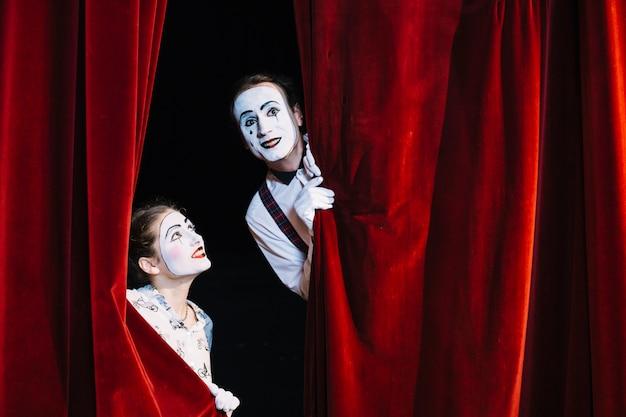Улыбающийся женский мим-художник, смотрящий на мужчину-миме художника, выглядывающего из занавеса