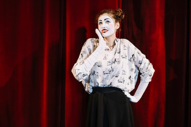 Smiling female mime artist standing in front of red curtain daydreaming
