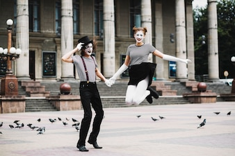 Smiling female mime holding male mime's hand jumping in front of building