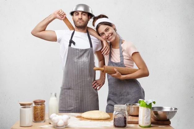 Il modello femminile sorridente in grembiule si appoggia alla spalla del marito, riceve aiuto e sostegno da lui