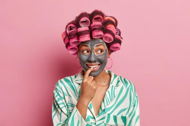 Улыбающаяся женщина-модель держит указательный палец возле зубов, заботится о цвете лица, наносит косметическую глиняную маску, делает прическу, одетую в домашнюю одежду, изолированную над розовой стеной. косметология