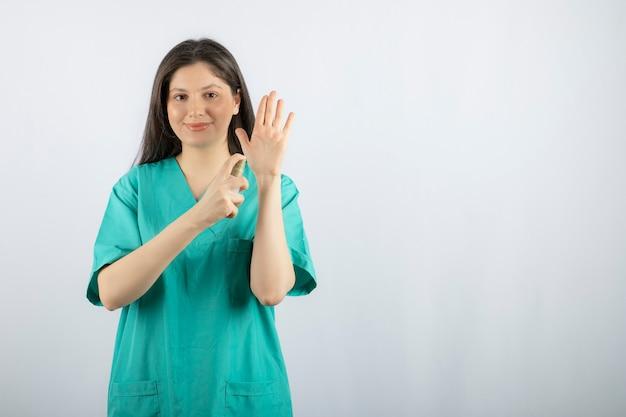 白に手をスプレーする笑顔の女性看護師。
