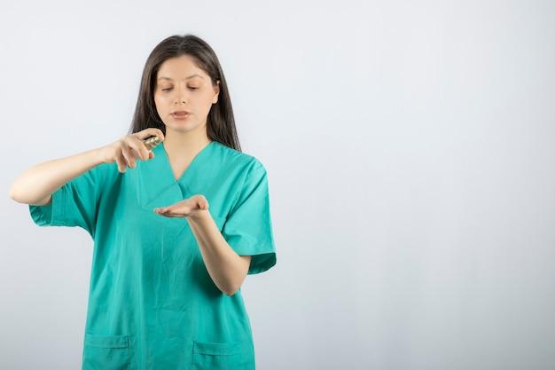 Smiling female nurse spraying her hand on white.