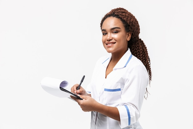 Smiling female nurse writing medical case report isolated against white wall