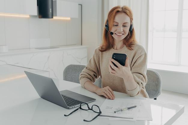 Улыбающийся женский офисный работник в гарнитуре с помощью смартфона, сидя на своем рабочем месте с ноутбуком